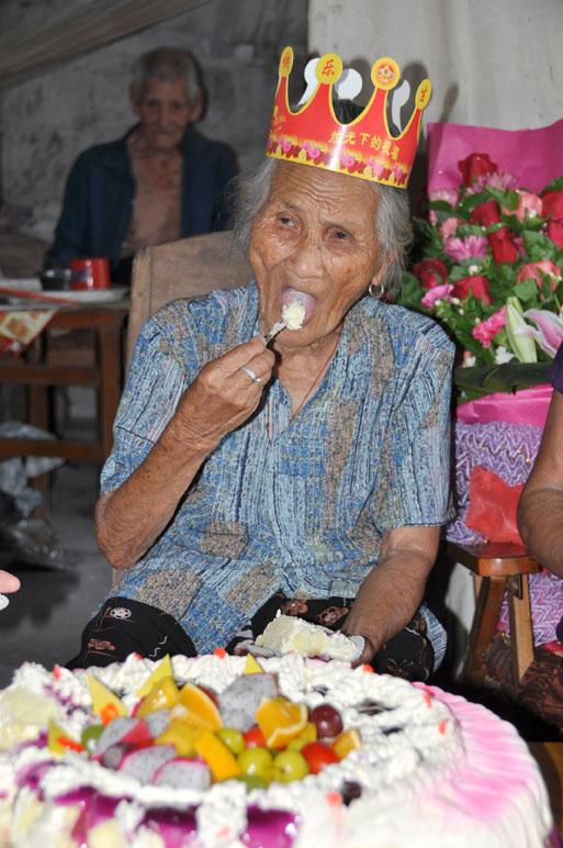 东兴市/李世英老人正在津津有味地吃着生日蛋糕。