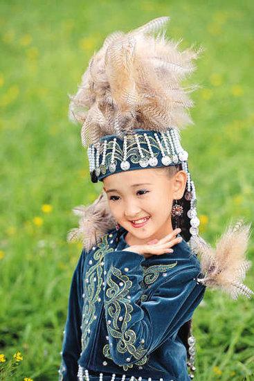 一名身着盛装的哈萨克族小女孩展示民族服饰