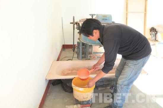 工人将研磨好的木浆舀入桶中