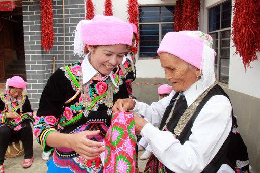 峨山彝族妇女向老人学习刺绣技艺。  精美艳丽的峨山彝绣产品。   不长树的山不算山,不会绣花的女子不算彝家女。生活在云南峨山的彝族女孩子,自幼学习刺绣。从简单的花边、单一的绣片开始绣起,再到手帕、鞋垫、头巾、围腰,直到绣出节日盛装、婚嫁礼服。闲暇时间,彝家女子会三五成群地围坐在一起,谈笑风生,飞针走线。   据考证,峨山彝绣至今已有1700多年的历史。在如水的光阴中,勤劳聪慧的峨山彝家女创制出纳苏堆绣、聂苏挑绣、山苏平绣、花腰贴绣等多种技法,以及长短针、套针、打籽针等十余种针法,形成了独具特色的峨山彝