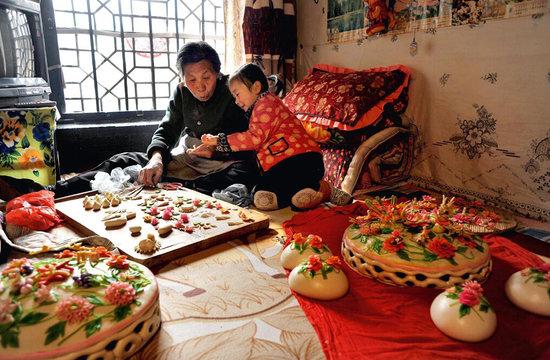 在陕西许多地区,花馍制作技艺代代相传。  孩子满月时制作的圈圈子花馍。  栩栩如生的群龙花馍。       中国的饮食文化源远流长、丰富多彩。流行于西北的民间花馍面食品,就是这一文化的典型代表。它伴随百姓生活而生,依附民俗风情而传承,特别是春节来临和婚庆嫁娶之时,更是少不了这种馒头工艺品。   花馍艺术在我国历史悠久,在黄河流域各省得到广泛传承和发展。陕西花馍又称礼馍、面花,其实就是花样馒头,盛行于关中和陕北。中国的面塑艺术早在汉代就有文字记载,它起源于民间祭祀活动中用面塑动物代替宰杀牛