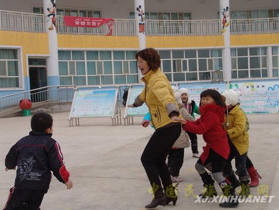 教师与幼儿园的孩子一起做游戏