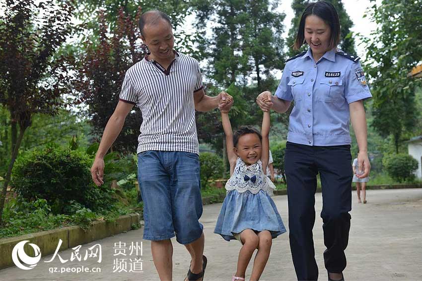 下雨天国内孩子父母抱着上幼儿园图片