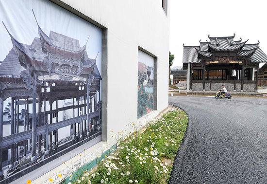 5月17日,在安徽蚌埠古民居博览园内,工人路过一处经修复重建的古戏台.